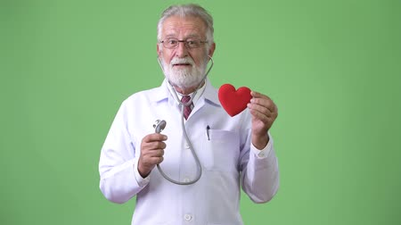 cardiologista : Handsome senior bearded man doctor against green background