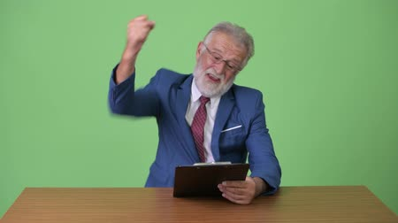 raising fist : Handsome senior bearded businessman against green background