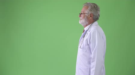 yandan görünüş : Handsome senior bearded man doctor against green background
