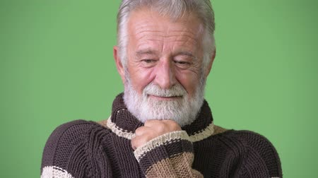 hand on chin : Handsome senior bearded man wearing warm clothing against green background
