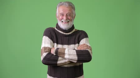 crossed : Handsome senior bearded man wearing warm clothing against green background