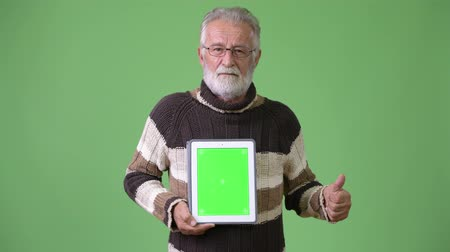 white shirt : Handsome senior bearded man wearing warm clothing against green background