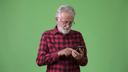 клетчатый : Handsome senior bearded man against green background