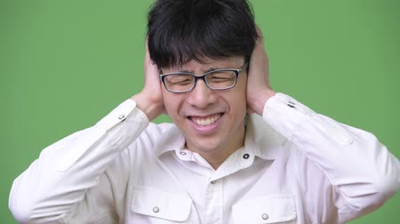 barulhento : Young Asian businessman covering ears while blocking loud noises Stock Footage