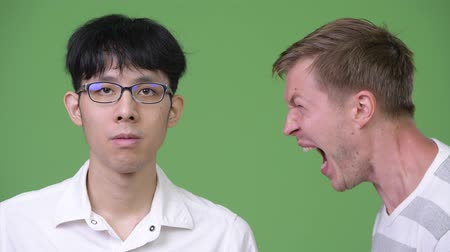 çığlık atan : Young angry Scandinavian businessman screaming at young Asian businessman