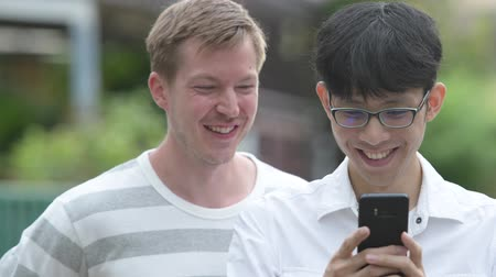 together trust : Two happy multi-ethnic businessmen using phone together in the streets outdoors Stock Footage