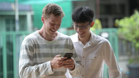 together trust : Two happy multi-ethnic businessmen smiling while using phone together in the streets outdoors