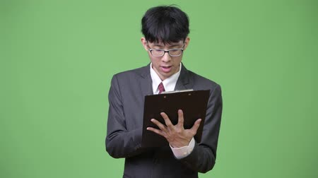 lista de verificação : Young Asian businessman reading with clipboard and talking to the side