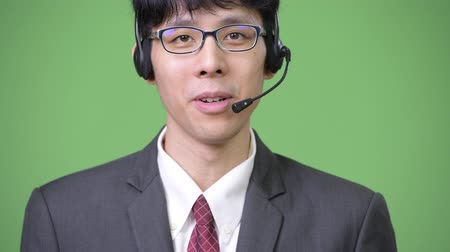 representante : Young Asian businessman smiling and working as call center representative Vídeos