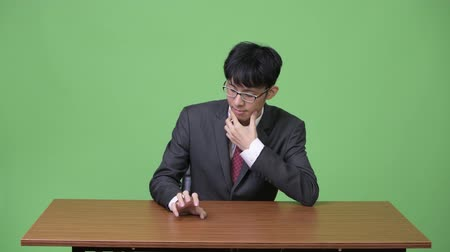 unalom : Young Asian businessman bored and tapping fingers on table Stock mozgókép