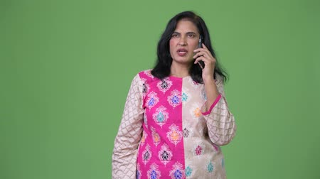phone call screen : Mature beautiful Indian woman thinking while talking on the phone