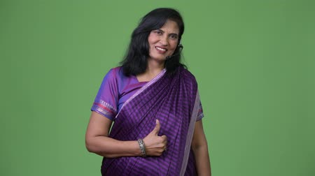 representante : Mature happy beautiful Indian woman as call center representative smiling while giving thumbs up Vídeos