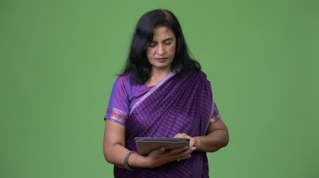 hinduismus : Mature beautiful Indian woman using digital tablet Dostupné videozáznamy