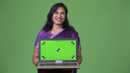 representante : Mature happy beautiful Indian woman as call center representative showing laptop