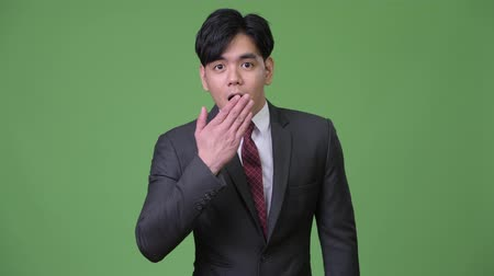 covering : Young handsome Asian businessman looking shocked