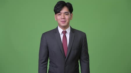 átnyújtás : Young happy Asian businessman smiling while talking to camera