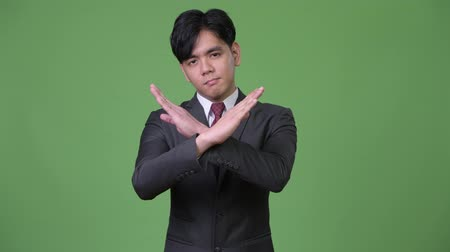 crossed : Young handsome Asian businessman gesturing to stop Stock Footage