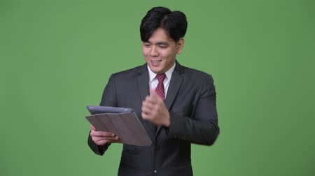 raising fist : Young handsome Asian businessman using digital tablet
