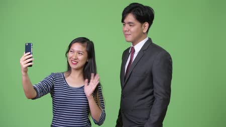 phone call screen : Young handsome Asian businessman and young Asian woman working together Stock Footage