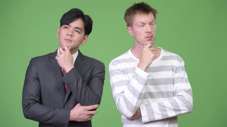 hand on chin : Young handsome Asian businessman and young Scandinavian businessman working together