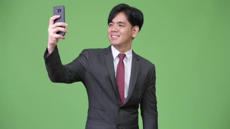 güneydoğu : Young handsome Asian businessman using mobile phone Stok Video