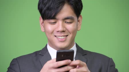sudeste : Young handsome Asian businessman using mobile phone Vídeos