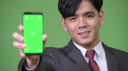 güneydoğu : Young handsome Asian businessman showing mobile phone