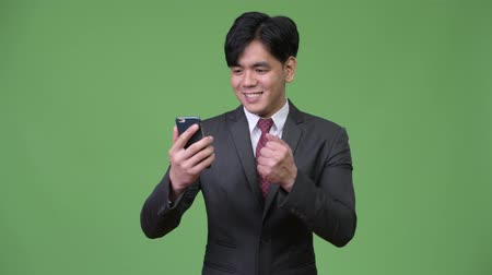 raising fist : Young handsome Asian businessman using mobile phone Stock Footage