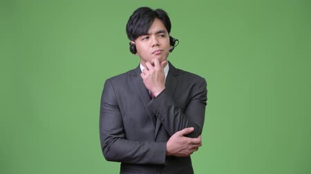 hand on chin : Young handsome Asian businessman working as call center representative Stock Footage