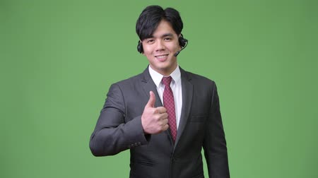 телемаркетинг : Young handsome Asian businessman working as call center representative Стоковые видеозаписи