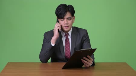 panoya : Young handsome Asian businessman working with clipboard against green background