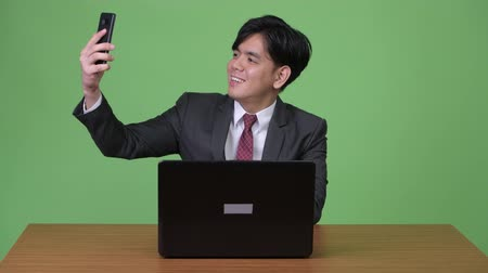 phone call screen : Young handsome Asian businessman working with laptop against green background