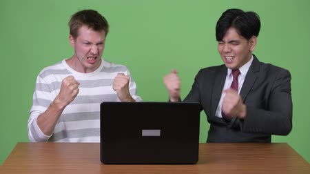 raising fist : Young Asian businessman and young Scandinavian businessman working together with laptop