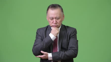 hand on chin : Mature stressed Japanese businessman looking down while thinking