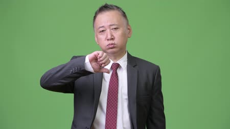 unalom : Mature Japanese businessman giving thumbs down Stock mozgókép