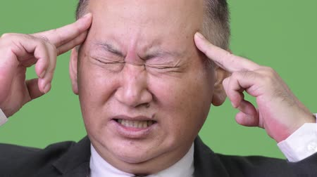 olhos fechados : Mature Japanese businessman having headache Stock Footage