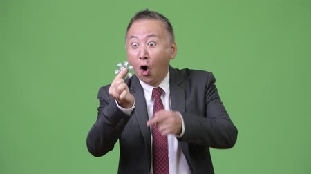 fidget spinner : Mature Japanese businessman playing with fidget spinner