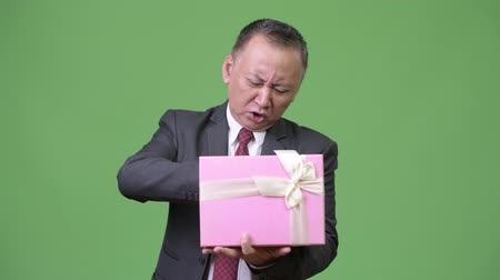 poo : Mature Japanese businessman with gift box against green background