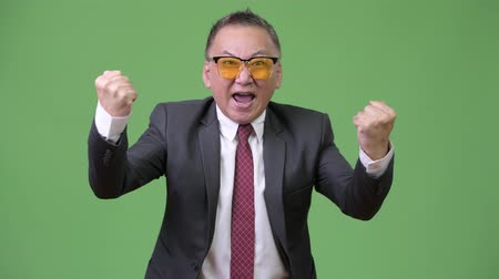 raising fist : Mature Japanese businessman wearing sunglasses against green background