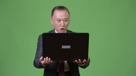 удивленный : Mature Japanese businessman working with laptop Стоковые видеозаписи