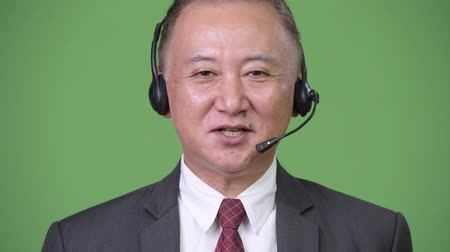 телемаркетинг : Mature Japanese businessman working as call center representative against green background