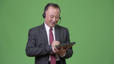 representante : Mature Japanese businessman working as call center representative against green background
