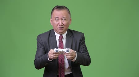 raising fist : Mature Japanese businessman playing games against green background