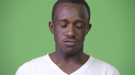 sem problemas : Young African man nodding no against green background Stock Footage