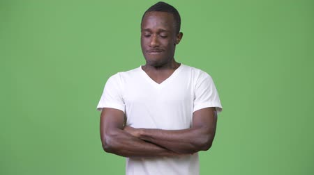 olhos fechados : Young African man looking angry with arms crossed and eyes closed Stock Footage