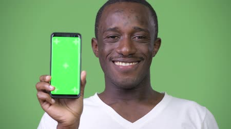 kısa : Young happy African man smiling while showing phone to camera Stok Video