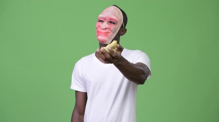 dışkı : Young African man holding poo while wearing mask and showing middle finger