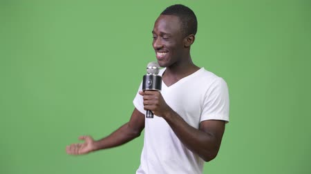 караоке : Young happy African man smiling while speaking on microphone