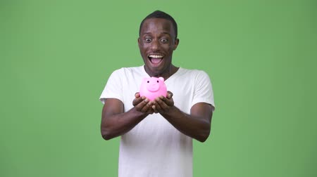 piggy bank : Young African man holding piggy bank