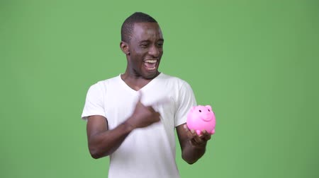 piggy bank : Young African man holding piggy bank and giving thumbs up Stock Footage